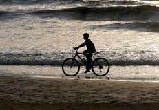 Silueta de un muchacho que monta una bici a lo largo del océano Foto de archivo