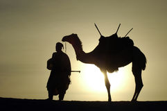 Silueta de un nómada y de un camello Foto de archivo libre de regalías