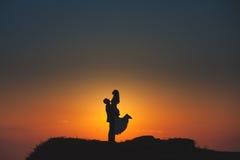 Silueta de un par cariñoso en el fondo del sol poniente Imagen de archivo libre de regalías