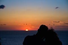 Silueta de un par cariñoso en el fondo del sol poniente, de las islas y del mar Santorini Grecia Imagen de archivo