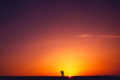 Silueta de un par cariñoso en la puesta del sol imagen de archivo