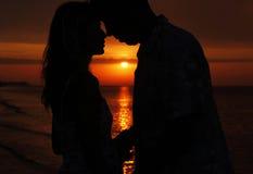 Silueta de un par cariñoso en la puesta del sol Fotografía de archivo libre de regalías