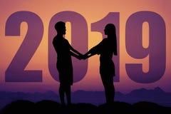 Silueta de un par del amor en la puesta del sol con el Año Nuevo 2019 foto de archivo libre de regalías