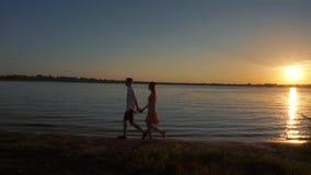 Silueta de un par en amor en un fondo tropical de la puesta del sol metrajes
