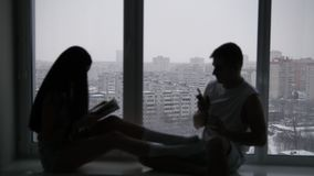 Silueta de un par feliz joven que se sienta en la ventana delante del día de invierno nevoso metrajes