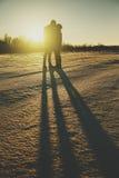 Silueta de un par joven que se besa en la gente de la puesta del sol Fotografía de archivo libre de regalías