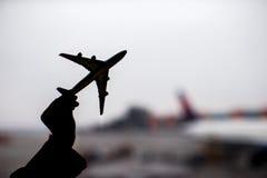 Silueta de un pequeño modelo del aeroplano en fondo del aeropuerto Fotos de archivo