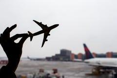 Silueta de un pequeño modelo del aeroplano en fondo del aeropuerto Foto de archivo