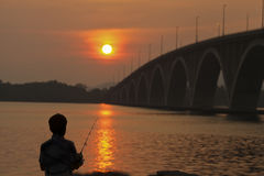 Silueta de un pescador imagenes de archivo