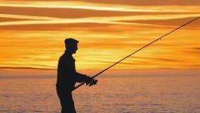Silueta de un pescador con una caña de pescar en la puesta del sol sobre el mar almacen de metraje de vídeo