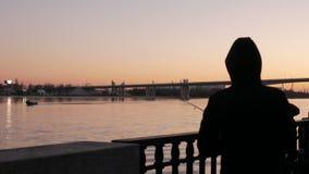 Silueta de un pescador en la puesta del sol Un hombre con una caña de pescar por el río almacen de metraje de vídeo