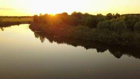 Silueta de un pescador en un barco en un río en la puesta del sol almacen de metraje de vídeo