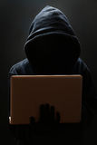 Silueta de un pirata informático que mira en monitor Imágenes de archivo libres de regalías