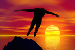 Silueta de un salto del hombre en puesta del sol Imagen de archivo libre de regalías