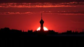 Silueta de un top de una iglesia una puesta del sol de color rojo oscuro imágenes de archivo libres de regalías