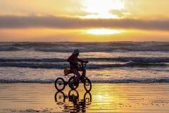 Silueta de un triciclo del montar a caballo de la muchacha en una playa en una marea que comienza imagenes de archivo