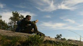 Silueta de un turista masculino joven que toma imágenes con un smartphone por la tarde en una aventura el vacaciones almacen de metraje de vídeo