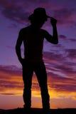 Silueta de un vaquero en un top sin mangas que toca su sombrero Fotografía de archivo libre de regalías