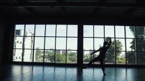 Silueta de un varón del bailarín de ballet contra la perspectiva de una ventana grande el bailarín hace un salto de altura Cámara metrajes