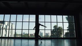 Silueta de un varón del bailarín de ballet contra la perspectiva de una ventana grande el bailarín hace un salto de altura y se m metrajes