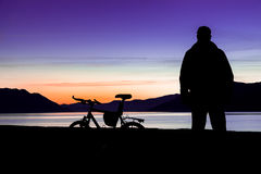 Silueta de una bici de montaña y de un ciclista en la puesta del sol Foco en la bici de montaña imagen de archivo libre de regalías