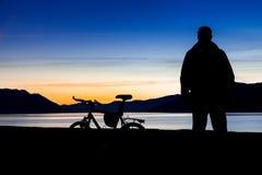 Silueta de una bici de montaña y de un ciclista en la puesta del sol Foco en la bici de montaña foto de archivo