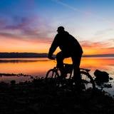 Silueta de una bici de montaña y de un ciclista en la salida del sol fotos de archivo