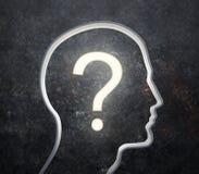 Silueta de una cara masculina con una pregunta que brilla intensamente Imagen de archivo libre de regalías