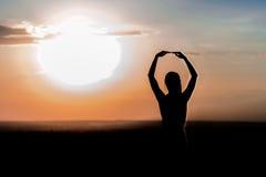 Silueta de una chica joven en el fondo de la puesta del sol Fotos de archivo libres de regalías