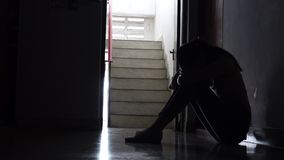 Silueta de una chica joven triste que se sienta en la oscuridad que se inclina contra la pared en propiedad horizontal vieja metrajes