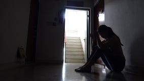 Silueta de una chica joven triste que se sienta en la oscuridad que se inclina contra la pared en la propiedad horizontal vieja,  almacen de metraje de vídeo