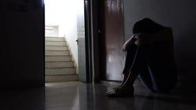 Silueta de una chica joven triste que se sienta en la oscuridad que se inclina contra la pared en la propiedad horizontal vieja,  almacen de video