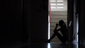 Silueta de una chica joven triste que se sienta en la oscuridad que se inclina contra la pared en la propiedad horizontal vieja,