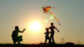 Silueta de una familia feliz durante puesta del sol Papá y dos niños que juegan con una cometa en naturaleza almacen de metraje de vídeo