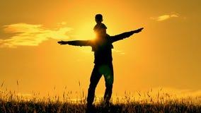 Silueta de una familia feliz en el fonaze del sol El padre detiene al niño en su hombro y juego, imitación almacen de metraje de vídeo