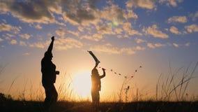 Silueta de una familia feliz que juega una cometa El abuelo y la niña están jugando en la puesta del sol con una cometa metrajes