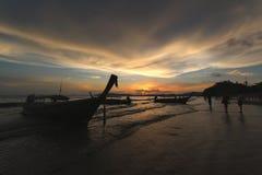 Silueta de una gente y de un barco por la playa Imagen de archivo libre de regalías
