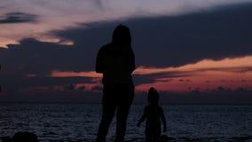 Silueta de una madre de la familia con un paseo del bebé en el mar de la puesta del sol foto de archivo