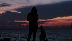Silueta de una madre de la familia con un paseo del bebé en el mar de la puesta del sol almacen de metraje de vídeo