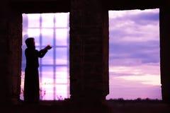 Silueta de una muchacha con una vela imagenes de archivo