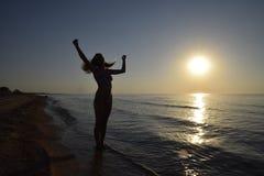 Silueta de una muchacha contra la puesta del sol por el mar Imagen de archivo