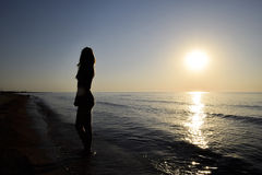 Silueta de una muchacha contra la puesta del sol por el mar Imágenes de archivo libres de regalías