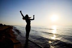 Silueta de una muchacha contra la puesta del sol por el mar Fotografía de archivo