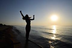 Silueta de una muchacha contra la puesta del sol por el mar Imagenes de archivo