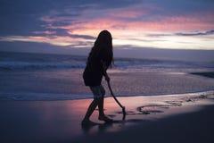 Silueta de una muchacha en puesta del sol Imágenes de archivo libres de regalías