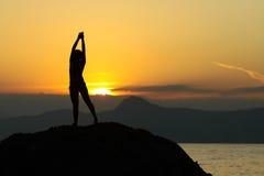 Silueta de una muchacha en un fondo de montañas sobre el mar Fotografía de archivo libre de regalías
