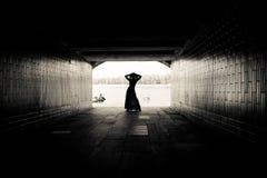Silueta de una muchacha en un túnel Imagen de archivo libre de regalías