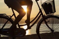 Silueta de una muchacha hermosa en una bicicleta Fotografía de archivo libre de regalías