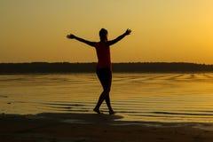 Silueta de una muchacha hermosa joven con las manos para arriba contra la perspectiva de la puesta del sol en la reflexión de la  imágenes de archivo libres de regalías