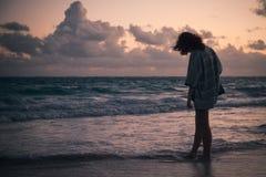 Silueta de una muchacha que camina en la costa del océano Imagen de archivo libre de regalías